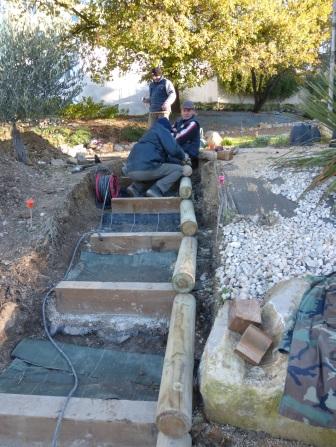 Mise en place de rondins en bois tournés pour délimiter l'escalier